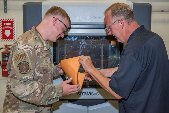 Staff Sgt. Cameron Canupp and Steven Conway, both of 412th Maintenance Squadron, visually inspects a part manufactured in a 3D printer at Edwards Air Force Base, California. (U.S. Air Force photo by Matthew Williams)