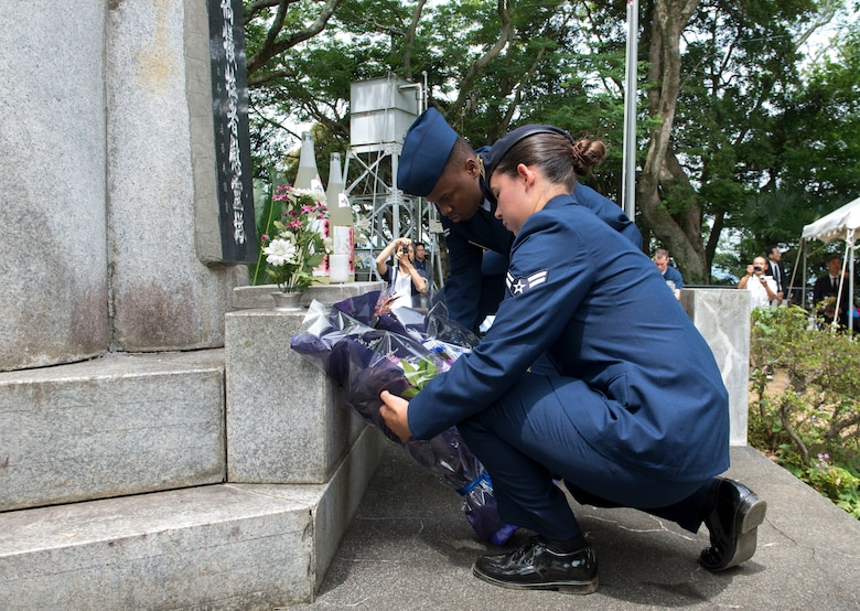 Airman 1st Class Veronica Hambel, 374th Security Forces Squadron patrolman (front), and Airman 1st Class John Mutiso, 374th Maintenance Operations Squadron documentation apprentice, lay flowers at the base of the Japanese memorial statue during the 47th annual B-29 Memorial Ceremony at Sengen Shrine in Shizuoka City, Japan, June 22, 2019.