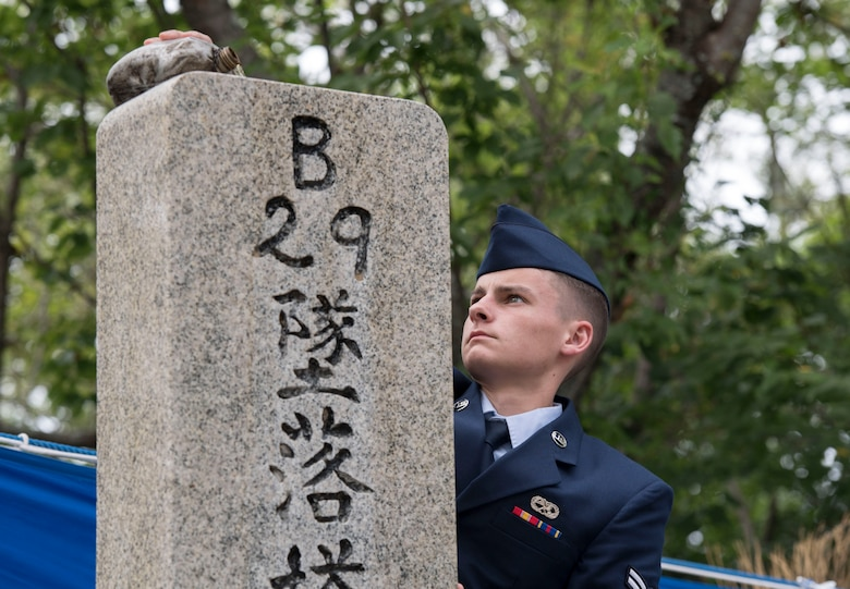 A Yokota Air Base Airman pours Bourbon over the American B-29 memorial monument during the 47th annual B-29 Memorial Ceremony at Sengen Shrine in Shizuoka City, Japan, June 22, 2019.