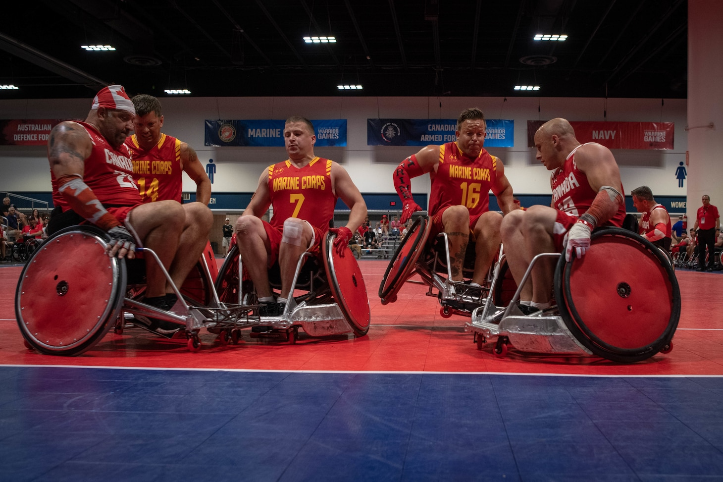 Group photo of athletes of Team Marine Corps and Canada colliding at the end zone during the 2019 DoD Warrior Games wheelchair rugby preliminaries in Tampa, Florida.