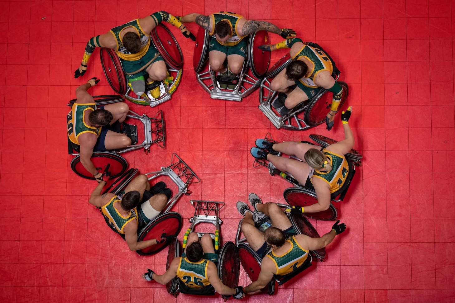 Overhead photo of Team Australia Wounded Warriors huddle in a circle at half time during the 2019 DoD Warrior Games wheelchair rugby preliminaries in Tampa, Florida.