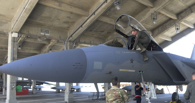 U.S. Air Force Brig. Gen. Case Cunningham, 18th Wing commander, climbs out of the cockpit of an F-15 Eagle after his final or fini flight as wing commander at Kadena Air Base, Japan, June 27, 2019.