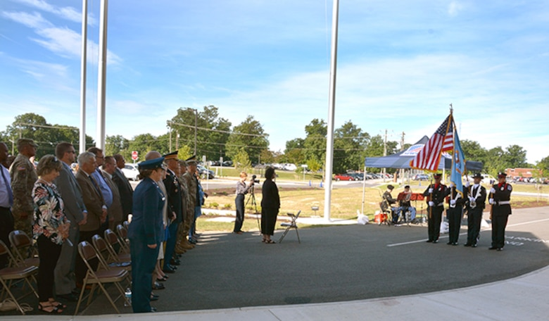 Audience stands for color guard at ribbon cutting ceremony
