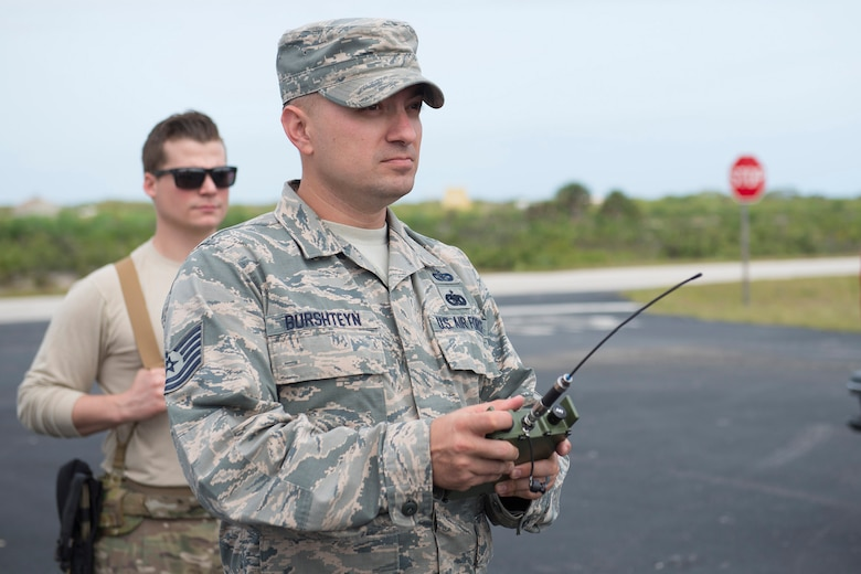 Tech. Sgt. Dmitriy Burshteyn, a field test team noncommissioned officer in charge with the Air Force Technical Applications Center, uses a remote firing device to detonate explosives while field testing new infrasound equipment at Cape Canaveral Air Force Station, Fla.  (U.S. Air Force photo by Matthew S. Jurgens)