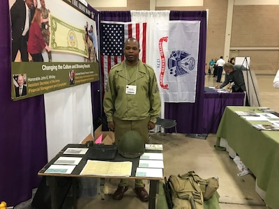 SSG(P) Njoroge, the 2019 Finance and Comptroller NCO of the Year, mans the ASA (FM&C) booth at the National PDI; 29-31 May 2019. He represented the members of the 136th Finance Disbursing Section (FDS) who landed on Omaha Beach in June, 1944. He is wearing an authentic WWII combat uniform with kit. On his field desk are Invasion Francs from D-Day.