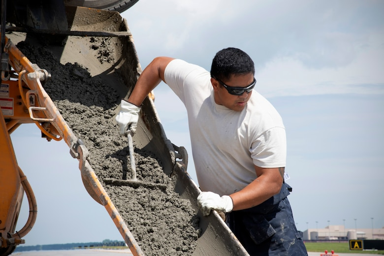 Staff Sgt. Newington Tamaalii, 319th Civil Engineer Squadron construction and pavement job lead, pushes out wet cement from a concrete mixer into a readied hole in the flightline June 25, 2019, on Grand Forks Air Force Base, North Dakota. As concrete begins to fill the hole in the ground, Newington's teammates worked hastily to spread and smooth it out as they saw fit. (U.S. Air Force photo by Senior Airman Elora J. Martinez)