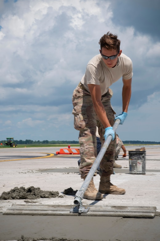 Senior Airman Brody Powell, 319th Civil Engineer Squadron construction and pavement journeyman, smooths over freshly-poured concrete on the flightline June 25, 2019, on Grand Forks Air Force Base, North Dakota. The 319 CES construction and pavement shop is responsible for horizontal construction during the warmer months, and mission-essential snow removal during the winter. (U.S. Air Force photo by Senior Airman Elora J. Martinez)