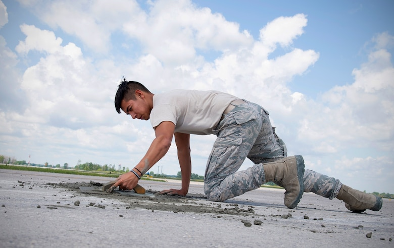 Senior Airman Job Hernandez, 319th Civil Engineer Squadron construction and pavement journeyman, screeds concrete on the flightline June 25, 2019, on Grand Forks Air Force Base, North Dakota. Hernandez worked alongside other members of the 319 CES to pour, smooth and finish concrete on a portion of the flightline in order to reactivate it for flight operations. (U.S. Air Force photo by Senior Airman Elora J. Martinez)