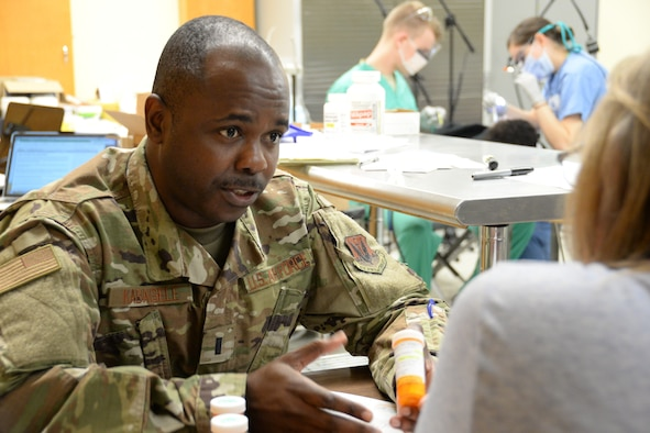 U.S. Air National Guard 1st Lt. Freddy Kabasele-Kalonji, the Cairo site pharmacy officer in charge and a critical care nurse assigned to 175th Medical Group, Baltimore, Md., speaks with a patient about proper doses for medication during an Innovative Readiness Training mission in Cairo, Ill., June 20, 2019.