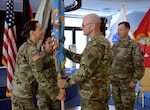 Air Force Maj. Gen. Allan Day, DLA Logistics Operations director, presents the colors to Army Col. Krista Hoffman, incoming DLA Europe & Africa commander, during a change of command ceremony June 26 in Kaiserslautern, Germany, as Army Master Sgt. Roxanna Carr (middle left), DLA E&A senior enlisted leader, and Army Col. Theodore Shinkle (right), outgoing commander, look on. Photo by Elisabeth Paqué