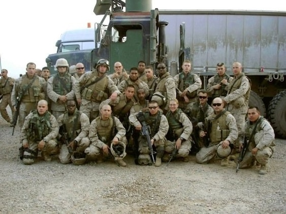 Vehicle Operator and Squad Leader poses with the 3rd Platoon, Combat Logistics Regiment 25, following a resupply convoy in 2005, in northern Iraq.