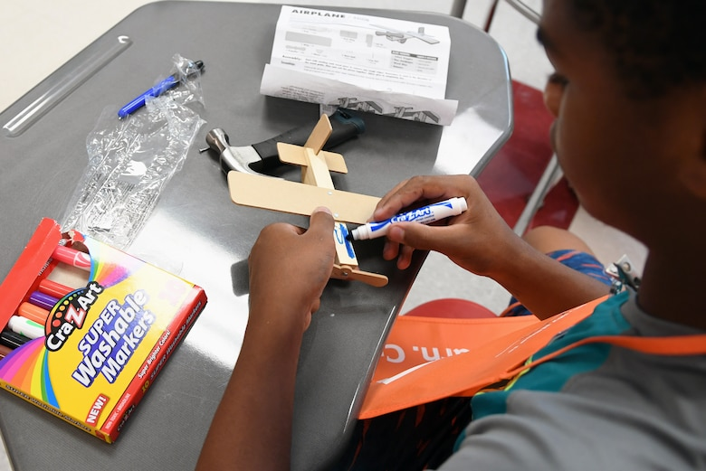Kaleb Foggie, Biloxi Junior High School eighth-grader, colors a wooden airplane after assembly during the Biloxi Public Schools Science, Technology, Engineering and Mathematics Summer Camp program at Biloxi High School in Biloxi, Mississippi, June 25, 2019. The four-day STEM summer program teaches first through seventh grade students skills for future careers and fosters valuable life skills like problem solving, creativity and collaboration. Keesler personnel volunteered their time to lead instructions on various projects. (U.S. Air Force photo by Kemberly Groue)
