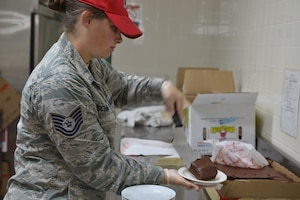 Technical Sgt. Kristin Schmidt, 210th REDHORSE, slices up some chocolate cake. The cake is the dessert that will compliment the lunch meal. This training was done on June 24, 2019 at Camp Pendelton, Va. (Photo by Master Sgt. Paula Aragon)