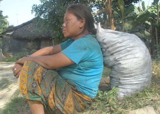 IMAGE: A woman in Beldangi-I camp in a deep look by resting on the sack of briquettees coals given for cooking purpose.