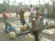 IMAGE: Refugees filling up vessels with water in camps