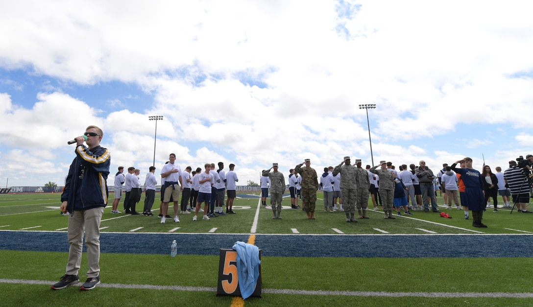 Conor Long sings the national anthem as members of Team Buckley render a salute June 22, 2019, in Highlands Ranch, Colorado.