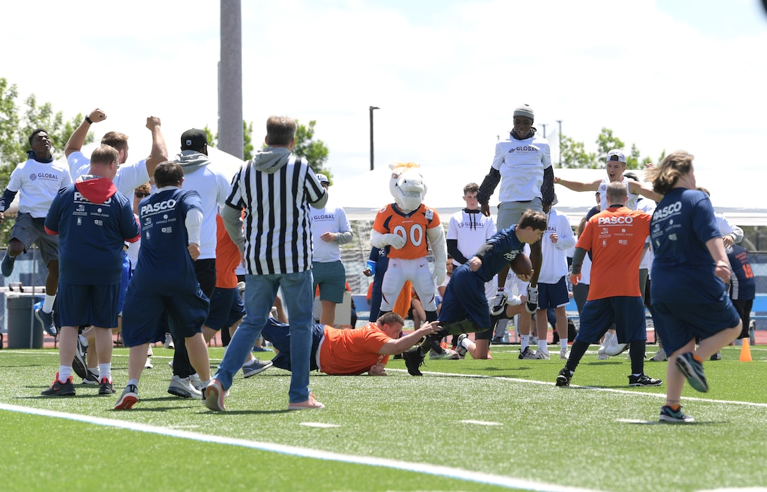 A player with the Orange Team tackles his opponent during the Dare to Play football event June 22, 2019, in Highlands Ranch, Colorado.