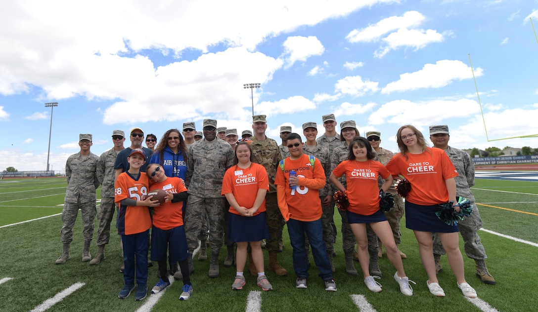 Members of Team Buckley pose for a group photo with players and cheerleaders following the 10th annual Dare to Play football event June 22, 2019, in Highlands Ranch, Colorado.