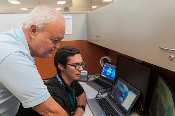 Fernando Rodriguez, left, BRAC program management division post transfer manager with the Air Force Civil Engineer Center's Base Realignment and Closure program, and Matthew Fischer access GeoBase at Joint Base San Antonio-Lackland, Texas, June 20, 2019. A BRAC team developed and transferred geospatial data for 39 BRAC installations onto the Air Force GeoBase, which centralizes all geospatial data and utilizes modern information procedures and technology to display and query data quickly and accurately. (U.S. Air Force photo by Malcolm McClendon)