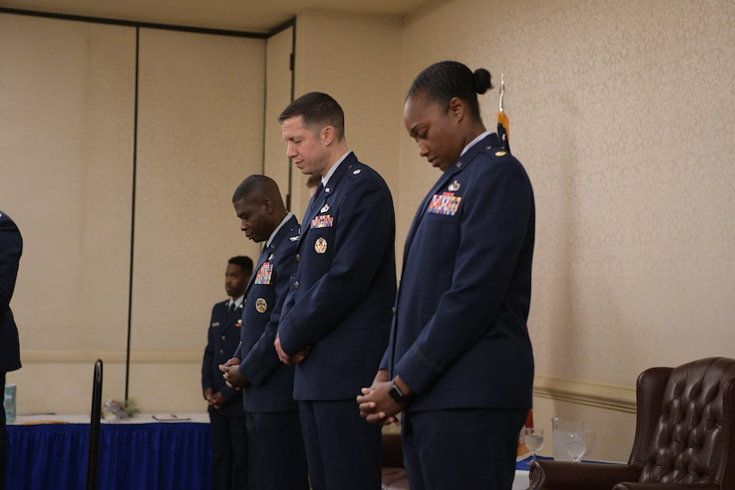 Left to right, Col. Adams, Lt. Col. Brian Collins and Maj. Jahayra N. Lowe bow their heads in prayer during the opening of the 628th Comptroller Squadron change of Command, June 27, 2019, at Joint Base Charleston, S.C. The squadron bid farewell to Collins, the outgoing commander, and welcomed Lowe as the new squadron commander. The change of command ceremony acts as a formal transfer of responsibility, authority and accountability from the outgoing to incoming commander.