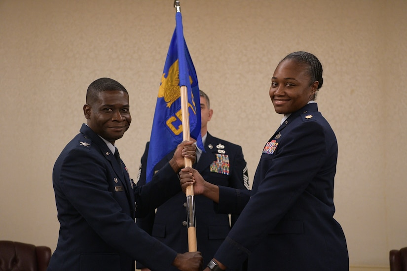 Col. Terrence Adams, 628th Air Base Wing commander, passes the 628th Comptroller Squadron guidon to Maj. Jahayra N. Lowe, 628th CPTS commander June 27, 2019 at Joint Base Charleston, S.C. The squadron bid farewell to Lt. Col. Bryan Collins, the outgoing commander, and welcomed Lowe as the new squadron commander. The passing of the guidon is a ceremonious representation of an incoming commander's assumption of command. The change of command ceremony acts as a formal transfer of responsibility, authority and accountability from the outgoing to incoming commander.