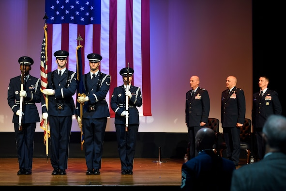 Four Airmen stand on stage during a ceremony