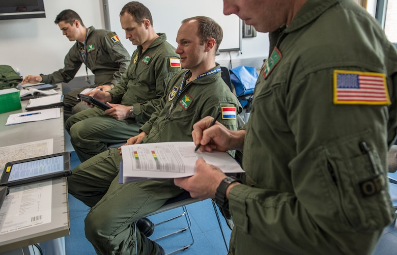 (Archive Photo) Aircrew from four countries take part in a mission brief before takeoff from Pápa Air Base, Hungary, March 23. The Strategic Airlift Capability program, a multinational mission, is comprised of 12 countries operating out of Pápa Air Base. The international unit is called the Heavy Airlift Wing, and is the first non-NATO unit of its kind. (U.S. Air Force Photo/Master Sgt. Brian Ferguson)