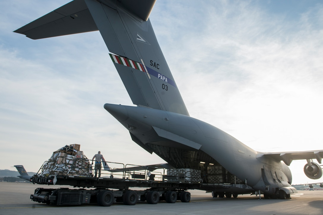 (Archive Photo) Load crews offload a C-17 Globemaster III on Ramstein Air Base, German, March 23. The Strategic Airlift Capability program, a multinational mission, is comprised of 12 countries operating out of Pápa Air Base, Hungary. The international unit is called the Heavy Airlift Wing, and is the first non-NATO unit of its kind. (U.S. Air Force Photo/Master Sgt. Brian Ferguson)