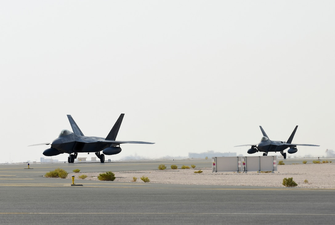 A photo of F-22s taxiing on a runway.