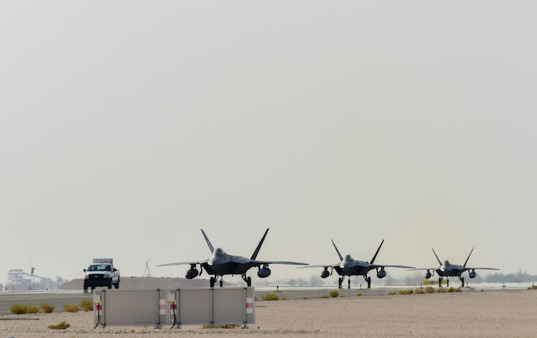 A photo of F-22s taxiing down a runway.