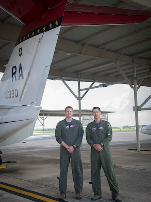 Maj. David Kim, 99th Flying Training Squadron Chief of Standardization and Evaluation and Maj. Joel Kliewer, 99th FTS pilot, pose in front of a T-1A Jayhawk. The T-1s sport a red stripe on the tail as a homage to their Tuskegee Airmen heritage. This resembles the red tails on the aircraft the original Tuskegee Airmen piloted as a way for their allies to spot them. (U.S. Air Force photo by: Airman 1st Class Shelby Pruitt)