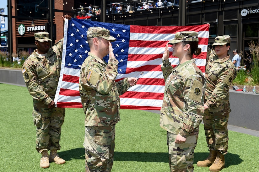 Sgt. Maribel Meraz, right, assigned to the 85th U.S. Army Reserve Support Command, headquartered in the northwest suburbs of Chicago, states the Oath of Enlistment at Gallagher Way, adjacent to the Chicago Cubs Wrigley Field, June 27, 2019, for a third six-years in the Army Reserve.