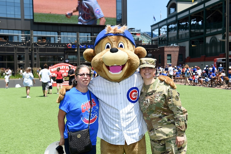 Sgt. Maribel Meraz, right, assigned to the 85th U.S. Army Reserve Support Command headquarters, pauses for a photo with her mother and Clark, Chicago Cubs mascot, at Gallagher Way, adjacent to the Chicago Cubs Wrigley Field, June 27, 2019, after reenlisting for a third six-years in the Army Reserve.