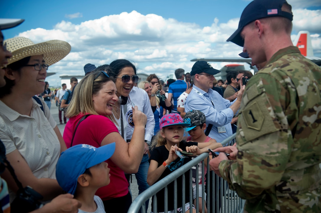 U.S. Army 1st Lt. Ryan Johnson, Bravo Troop, 1st Squadron, 6th Cavalry Regiment, 1st Combat Aviation Brigade, 1st Infantry Division, stationed at Fort Riley, Kan., trades patches with visitors to the Paris Air Show, June 21, 2019. The air show provided a collaborative opportunity to share and strengthen U.S. and strategic international partnerships. (U.S. Air Force photo by Master Sgt. Eric Burks)