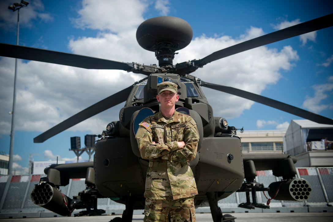 U.S. Army 1st Lt. Ryan Johnson, Bravo Troop, 1st Squadron, 6th Cavalry Regiment, 1st Combat Aviation Brigade, 1st Infantry Division, stationed at Fort Riley, Kan., poses for a photo in front of an AH-64E Apache helicopter from his unit at the Paris Air Show, June 21, 2019. Johnson was one of approximately 130 U.S. military aircrew and support personnel from bases in Europe and the U.S. who participated in the air show. (U.S. Air Force photo by Master Sgt. Eric Burks)