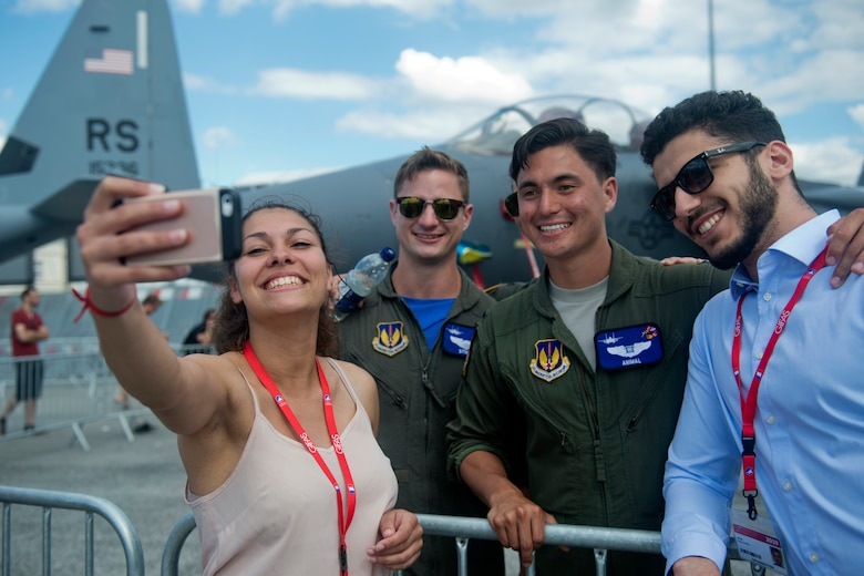 "U.S. Air Force 1st Lt. Brandon ""Animal"" Shelley, a 492nd Fighter Squadron weapon systems officer from the 48th Fighter Wing at Royal Air Force Lakenheath, England, poses for a photo with visitors in front of an F-15E Strike Eagle from his squadron at the Paris Air Show, June 21, 2019. Shelley was one of approximately 130 U.S. military aircrew and support personnel from bases in Europe and the U.S. who attended the air show. (U.S. Air Force photo by Master Sgt. Eric Burks)"