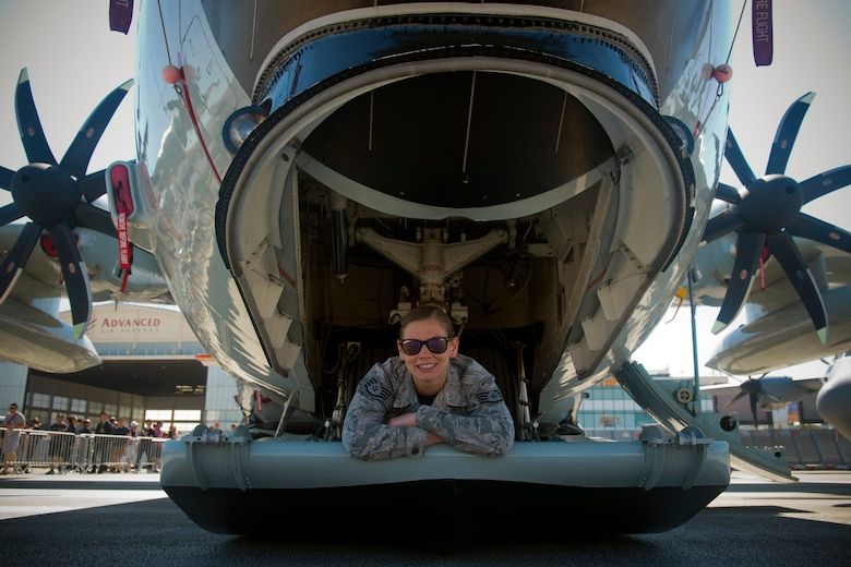 """U.S. Air National Guard Staff Sgt. Jennatte Berger, an avionics technician from the 109th Airlift Wing at Stratton Air National Guard Base in Scotia, N.Y., poses for a photo on the skis of an LC-130 Hercules """"Skibird"""" from her unit at the Paris Air Show, June 22, 2019. This year was the first time the 109th AW, or any New York Air National Guard contingent, had participated in the Paris Air Show. (U.S. Air Force photo by Master Sgt. Eric Burks)"""