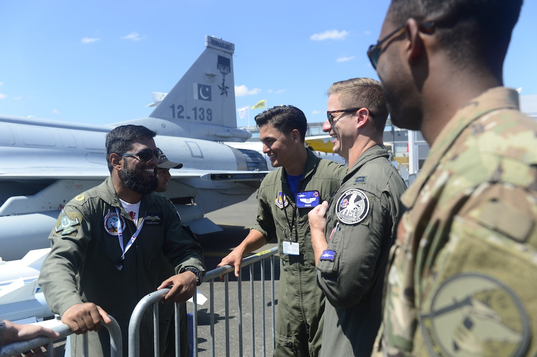"U.S. Air Force 1st Lt. Brandon ""Animal"" Shelley, a 492nd Fighter Squadron weapon systems officer from the 48th Fighter Wing at Royal Air Force Lakenheath, England, center, and other 48th FW Airmen engage with members of the Pakistan Air Force during the Paris Air Show at Le Bourget Airport, France, June 22, 2019. The air show provided a collaborative opportunity to share and strengthen U.S. and strategic international partnerships. (U.S. Air Force photo by Master Sgt. Eric Burks)"