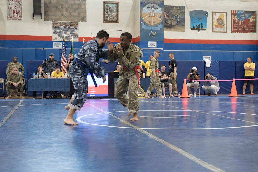 United States Army Spc. Luciano Thomas, right, a signal support systems specialist assigned to 18th Field Artillery Brigade, Headquarters and Headquarters Battery, competes in a combatives tournament at Camp Arifjan, Kuwait, June 23, 2019. U.S. Army Central hosts events such as the combatives tournament to strengthen its relationship and build partner capacity with the Kuwaitis. USARCENT operates throughout the Middle East region and appreciates the generosity of the host nation's willingness to maintain bilateral defense relationships.