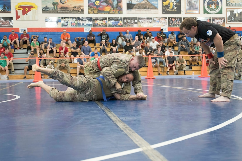 United States Army Sgt. Linsey Williams, bottom, a public affairs mass communications specialist assigned to the 34th Red Bull Infantry Division, Minnesota Army National Guard, maneuvers out of a hold by Capt. Joshua Harmon, a chaplain with 8th Battalion, 229th Aviation Regiment, during a combatives tournament at Camp Arifjan, Kuwait, June 23, 2019.  U.S. Army Central promotes good unit moral which enhances unit cohesion and reinforces the importance of excellence.