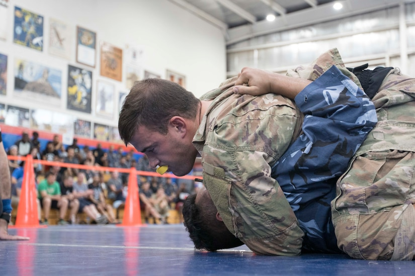 United States Army Cpl. Eric Stanley, 637th Chemical Company, Ohio Army National Guard, executes the Ezekiel choke during a combatives tournament at Camp Arifjan, Kuwait, June 23, 2019. U.S. Army Central hosts events such as the combatives tournament to strengthen its  relationship and build partner capacity with the Kuwaitis. USARCENT operates throughout the Middle East region and appreciates the generosity of the host nation's willingness to maintain bilateral defense relationships.
