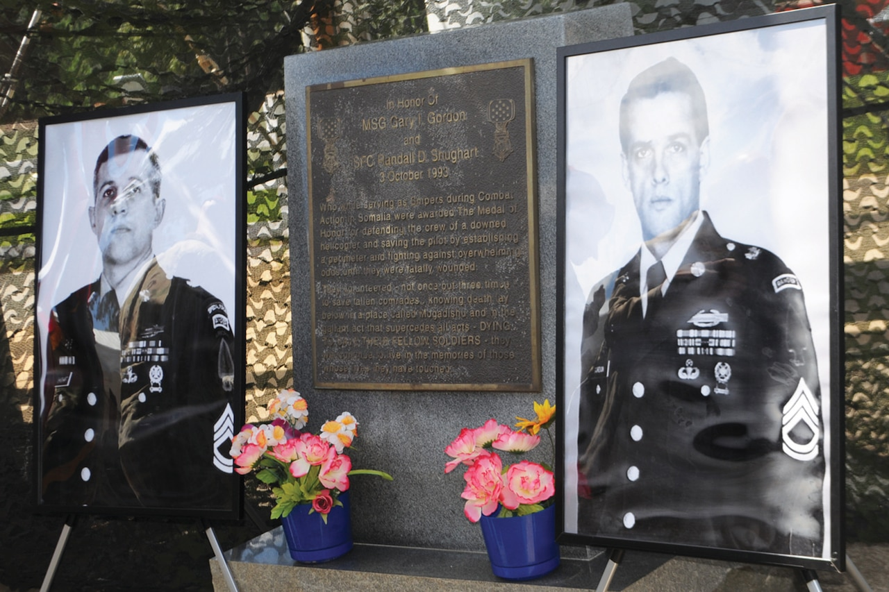 Two large portraits of soldiers in dress uniform are propped up beside a plaque honoring them. Flowers sit at the base of the plaque.