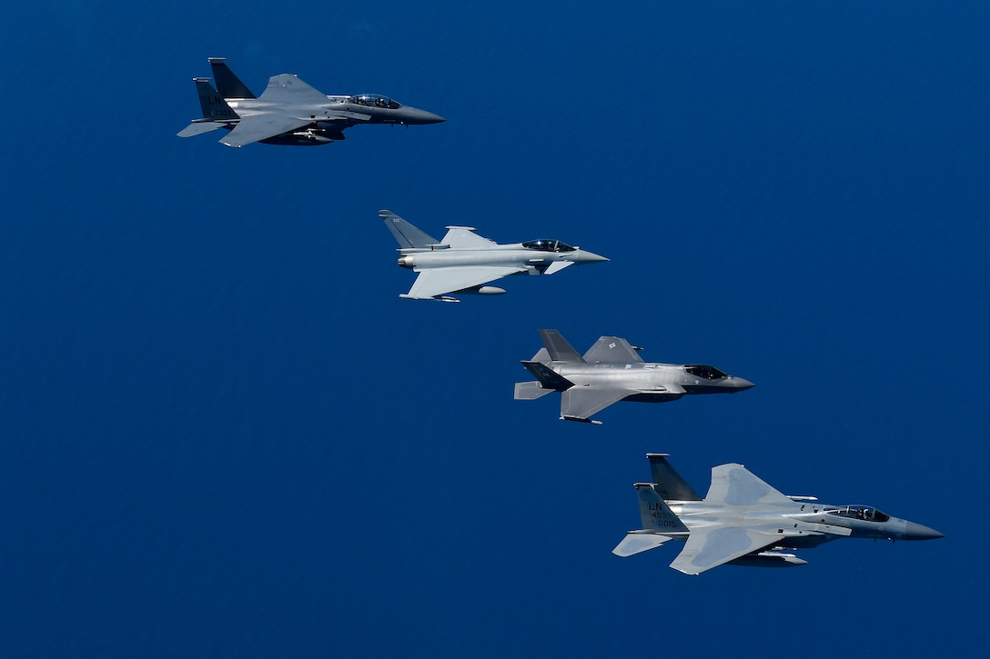 Fourth and fifth-generation aircraft fly in an echelon formation