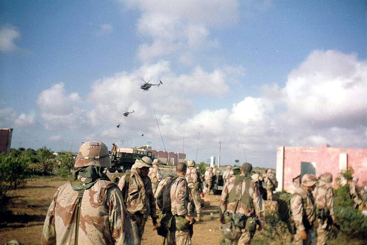 Several soldiers in desert camouflage look into the distant sky, where four Black Hawk helicopters are flying.