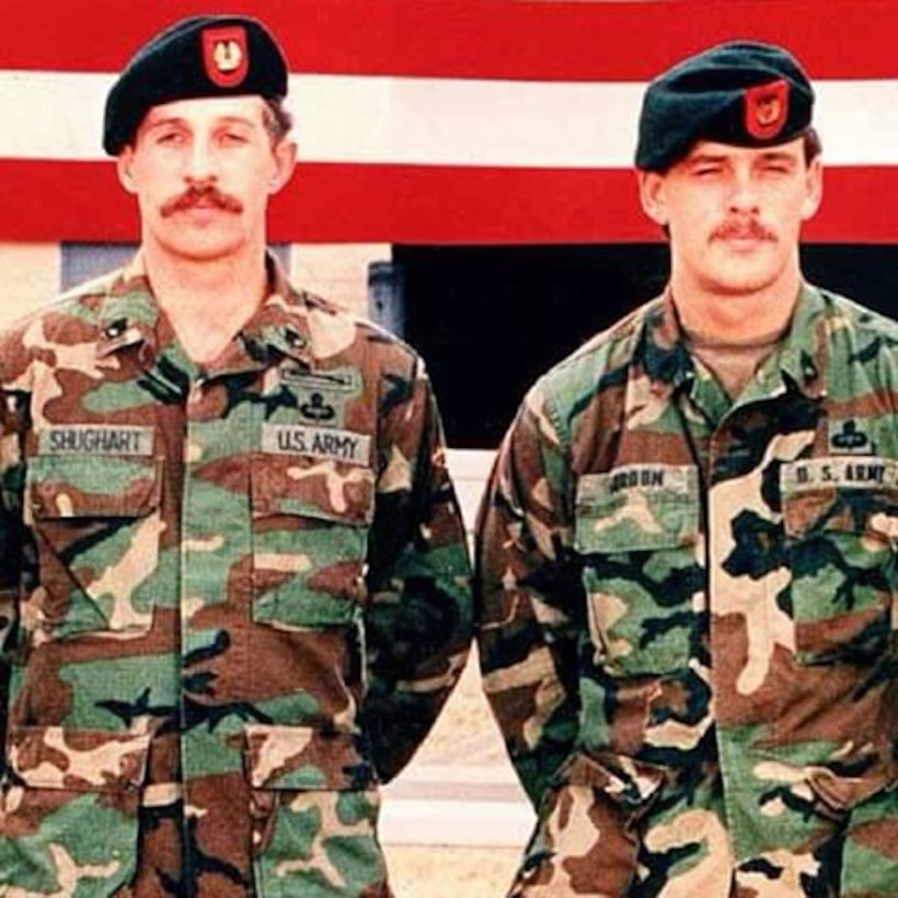 Two Delta Force soldiers wearing camouflage and black hats with red logos stand with their hands behind their backs in front of an American flag.