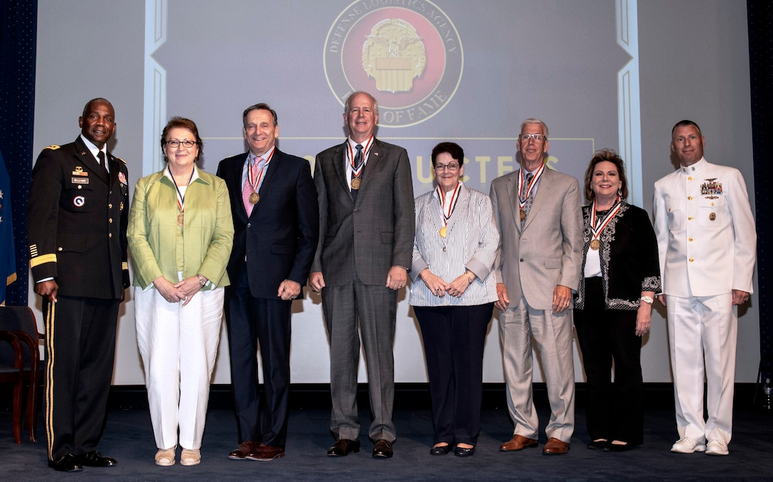 Five men and three women pose onstage at the 2019 DLA Hall of Fame ceremony.