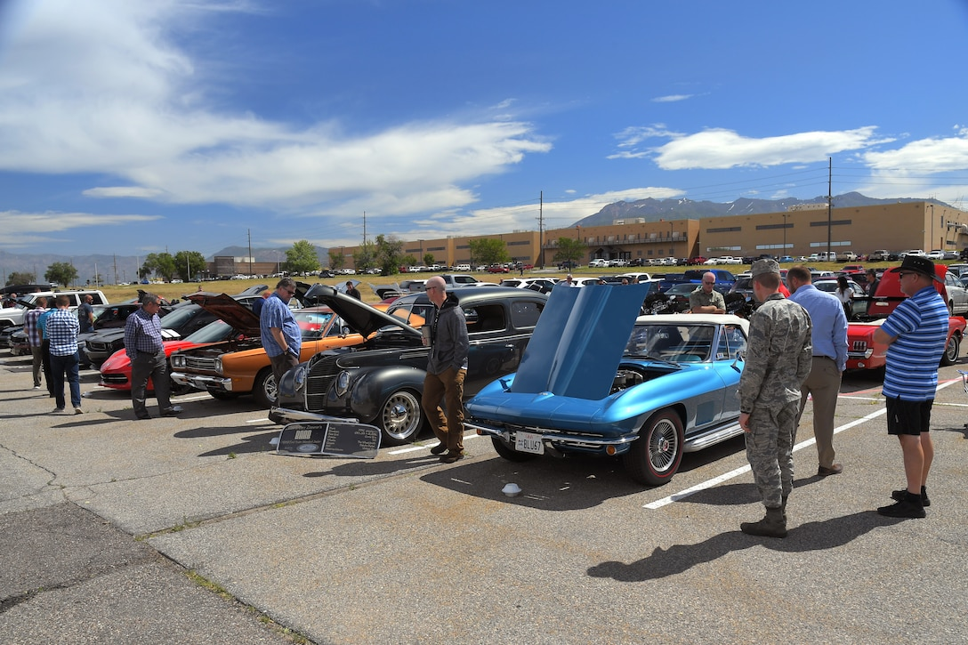 Guests enjoy a mix of modern and restored classics at a car show and barbecue hosted by the base's Foreign Military Sales organization at Hill Air Force Base, Utah, June 27, 2019. The event was a first for the unit, and several program teams and employees displayed and shared details with visitors about their personally owned vehicles. (U.S. Air Force photo by Todd Cromar)