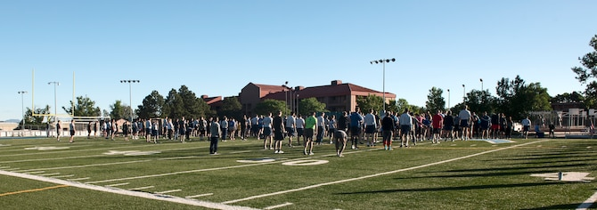 PETERSON AIR FORCE BASE, Colo.—Members of the 21st Space Wing gather on the football field at Peterson Air Force Base, Colorado, June 21, 2019 for stretches before a run. The Wing Warfit 5K takes place once a month as a morale event, often with varying themes. This month's theme was superheroes. (U.S. Air Force photo by Airman Alexis Christian)