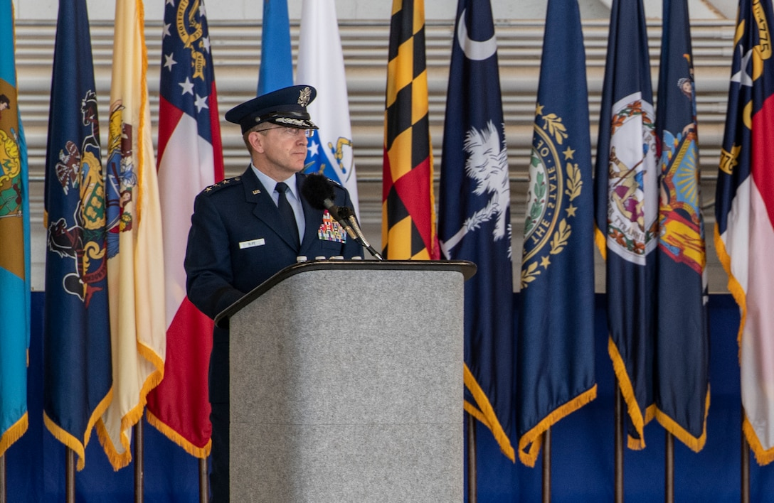One person speaking in front of multiple flags.