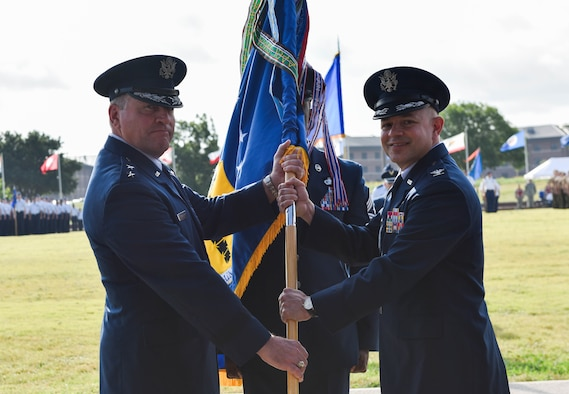 U.S. Air Force Maj. Gen. Timothy Leahy, Second Air Force commander, presents the guidon to incoming commander, Col. Andres Nazario, during the 17th Training Wing change of command ceremony at the parade field on Goodfellow Air Force Base, Texas, June 28, 2019. Leahy presided over the ceremony, in which Col. Ricky Mills relinquished command of the 17th TRW. (U.S. Air Force photo by Staff Sgt. Chad Warren/Released)
